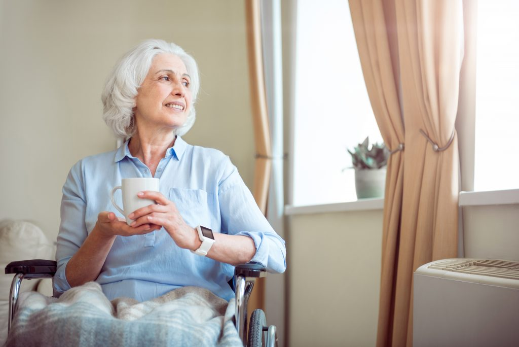 Positive and delighted old woman in wheelchair with cup of tea - Independent Living Solutions - Appello Independent Living Solutions